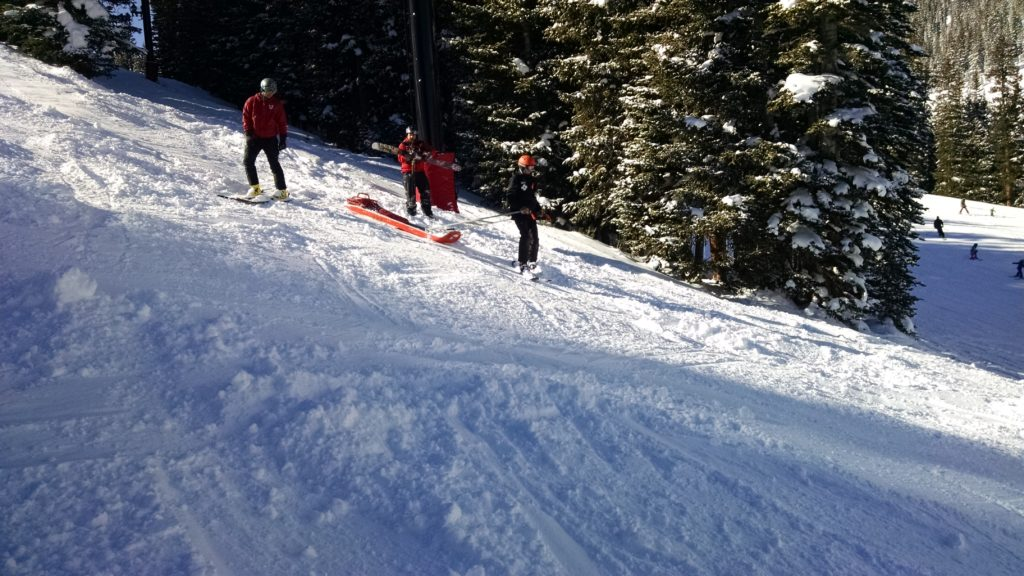 Nickolas Malwitz in ski patrol sled training while Jeff Malwitz and I pick our way down the bumps to check it out